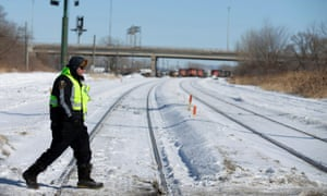 A police officer crosses the railway tracks in front of where protesters maintain a railway blockade in St-Lambert.