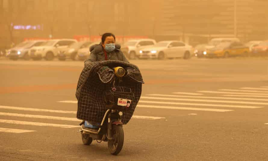 A woman wearing a mask rides a scooter during a sandstorm in Beijing, China