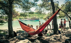 A festivalgoer relaxes in a hammock by the waterfront in a publicity image for the Love International festival at the Garden Resort in Tisno.
