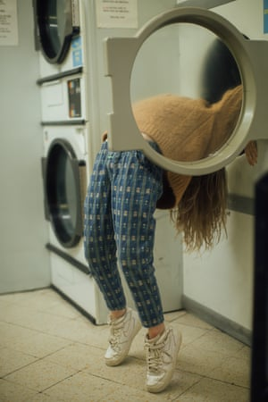 A girl bending backwards and leaning against a machine at the laundrette