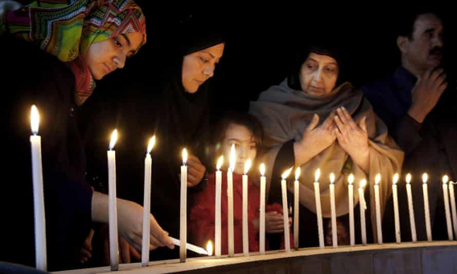Pakistani women light candles during a vigil for victims of the Bacha Khan university attack