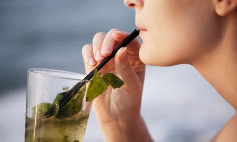 Cropped Image Of Woman Drinking MojitoExtreme close up of beautiful young woman enjoying an evening cocktail sitting overlooking a tropical beach with her face turned towards the setting sun