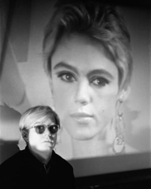 Warhol in his studio in front of one of the Beauty films featuring Edie Sedgwick, 1965.