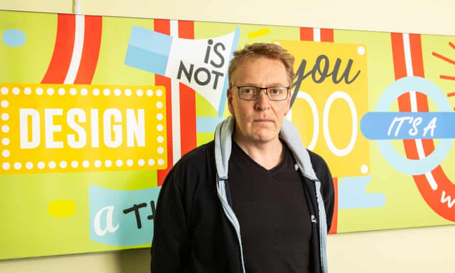 Portrait of Andrew Moss standing in front of a colourful wall sign