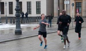 Facebook founder Mark Zuckerberg runs through Berlin with his personal bodyguards.