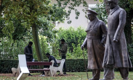 Migrants from Sudan sit near statues of Winston Churchill and Charles de Gaulle in a public park in Calais.