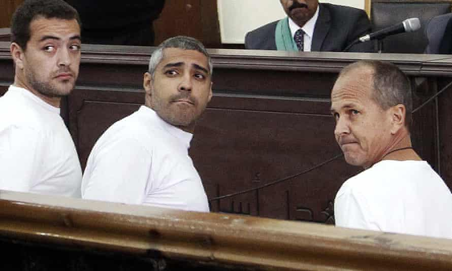 The now famous picture of Fahmy (centre), Baher Mohamed (left) and Peter Greste in court.