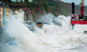 Stormy weather brings waves crashing over trains at Dawlish, Devon, UK, where repairs are still ongoing following damage to the sea wall in February 2014.