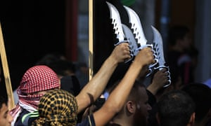 Palestinians in headscarves hold vicious-looking knives high in the air