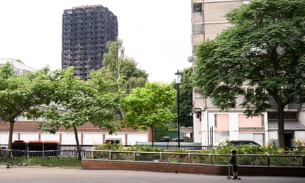 A boy looks towards the remains of Grenfell Tower.