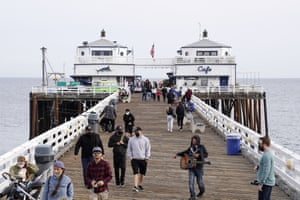 People walk on the Malibu Pier on Sunday as businesses reopen.