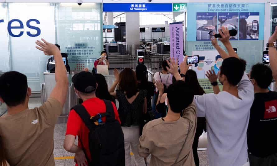 A woman takes photos of her friends before entering the departures hall for her flight to Britain