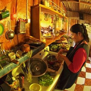 An Indigenous Mapuche women, preparing dinner in her kitchen