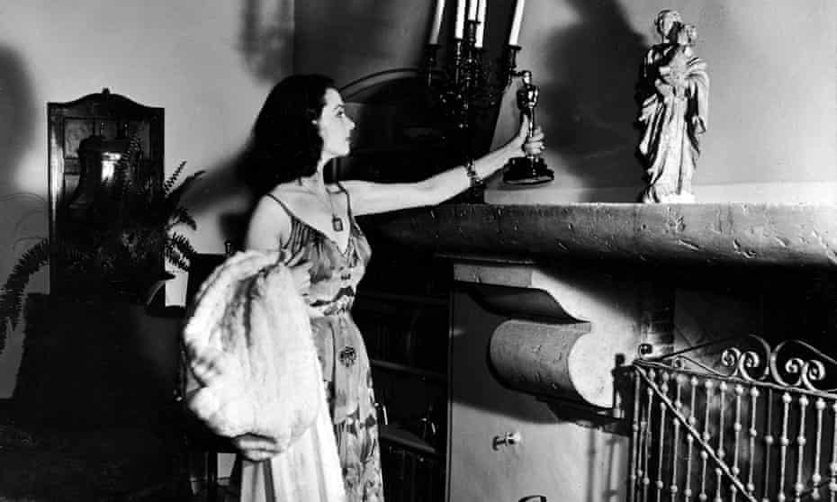 Vivien Leigh places her Oscar for best actress on the mantle in her living room, wearing her outfit from the awards ceremony.