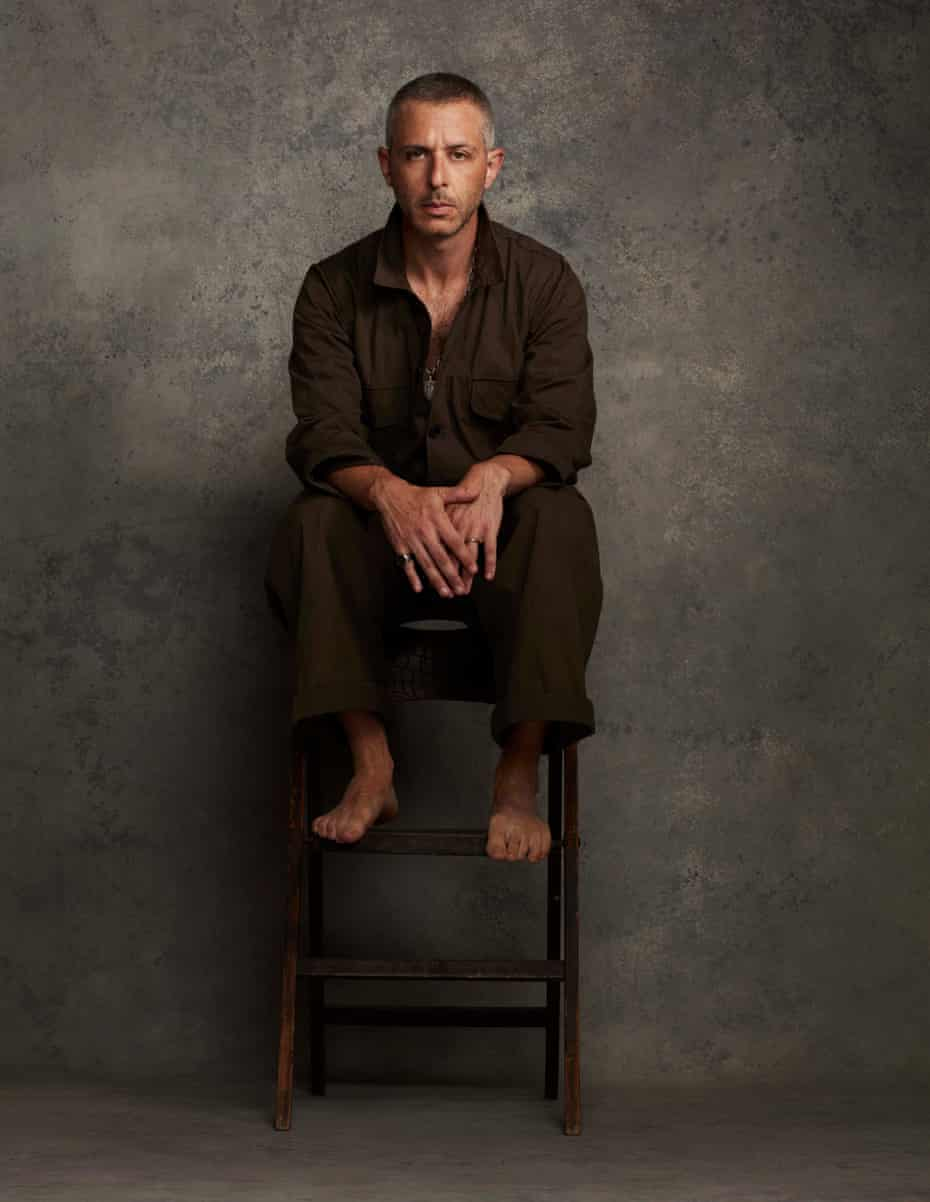 Jeremy Strong sitting on a high stool wearing an olive green jumpsuit