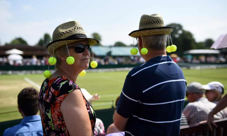 Fans wear tennis-themed sun hats as they wait for the play to start at Wimbledon