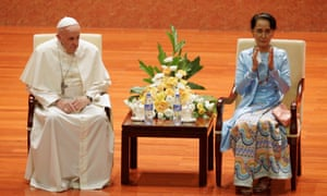 Aung San Suu Kyi applauds as she sits next to Pope Francis.