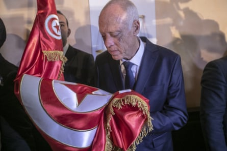 Independent candidate Kais Saied holds the Tunisian flag at a press conference after exit polls pointed to victory.