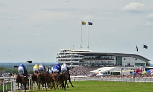 The runners and riders take the corner into the straight during the first race on Derby day.