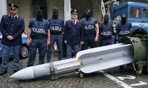 Police stand by a missile seized at an airport hangar
