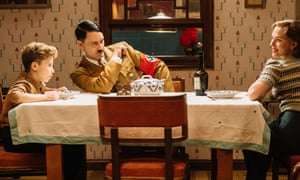 Adolf leans towards boy to look at mother over dinner table.