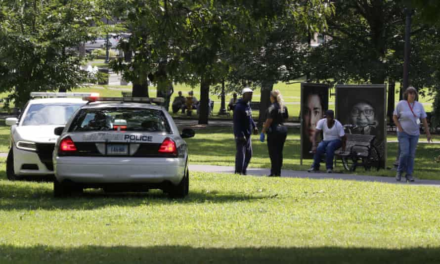 A police officer speaks to a man walking in New Haven Green park on 15 August. At least 95 people overdosed on the synthetic drug in the city over the course of two days.