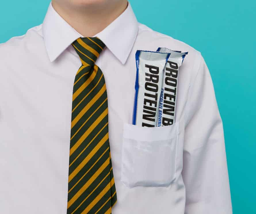 A photograph of a boy in a school shirt and tie with protein bars in his pocket