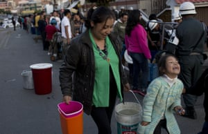 A woman walks with her daughter after filling her buckets with water, after military police distributed water to residents in La Paz