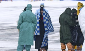 Medical personnel meet people evacuated by a Russian military plane at an airport outside Tyumen, Russia, on 5 February.