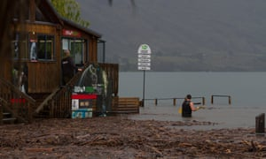 Michael Donald the owner of Lakeland Wanaka wades through flood waters in Wanaka
