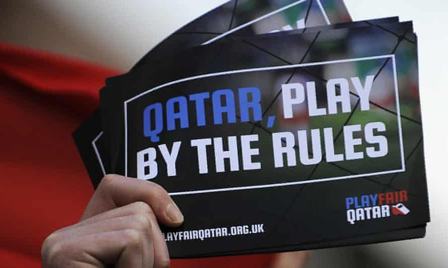 A fan holds a leaflet telling Qatar to play by the rules