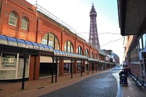 A pedestrian walks along an almost deserted shopping street, near the Blackpool Tower, in Blackpool, northwest England, on 25 January, 2021.