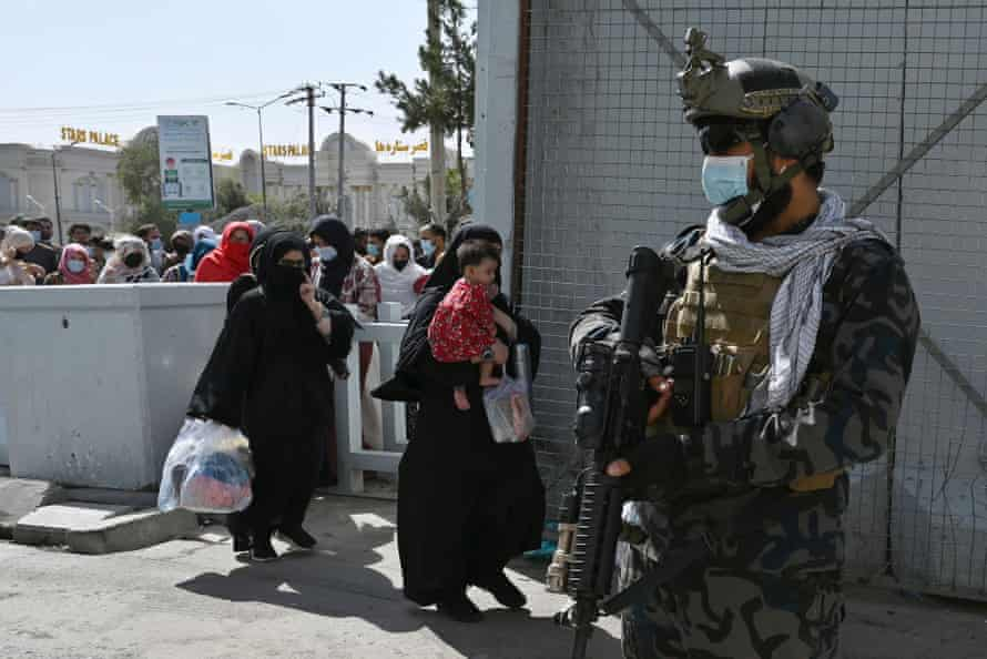 A member of Taliban Badri fighters, a 'special forces' unit, stands guard as Afghan walk thorough the main entrance gate of Kabul airport to leave Afghanistan in Kabul on Saturday.