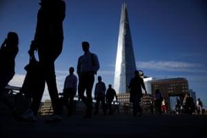 London: people walk across London Bridge during morning rush hour