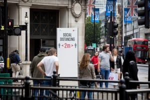 Shops on Oxford Street in central London near oxford Circus tube with signs requesting shoppers keep a 2m social distance from each other.