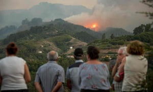 Smoke billows from a forest fire near Montaña Alta