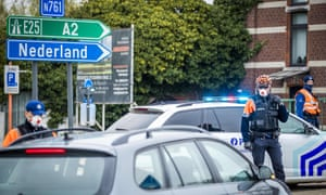 Police in protective masks stop motorists at the Dutch-Belgian border