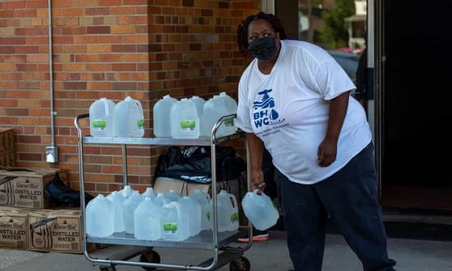 A volunteer prepares gallons of water to be distributed to residents at the Harbor Harvest Urban Ministries in Benton Harbor.