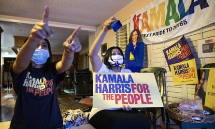 Harini Krishnan, right, and her daughter Johnny Krishnan celebrating with a poster promoting Jha Kamala Harris