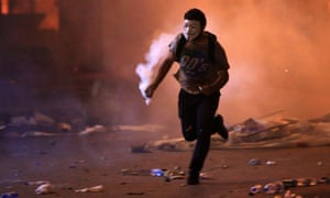 A masked demonstrator with a teargas canister amid clashes with security forces in the centre of Beirut
