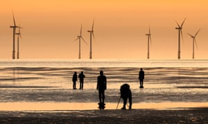 Silhouettes of a photographer and Anthony Gormleys Another Place iron men on Crosby beach. In background wind farm at burbo bank, windturbines, each of which is around 260 feet tall.