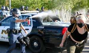 A police officer sprays a chemical irritant to clear protesters from a parking lot.