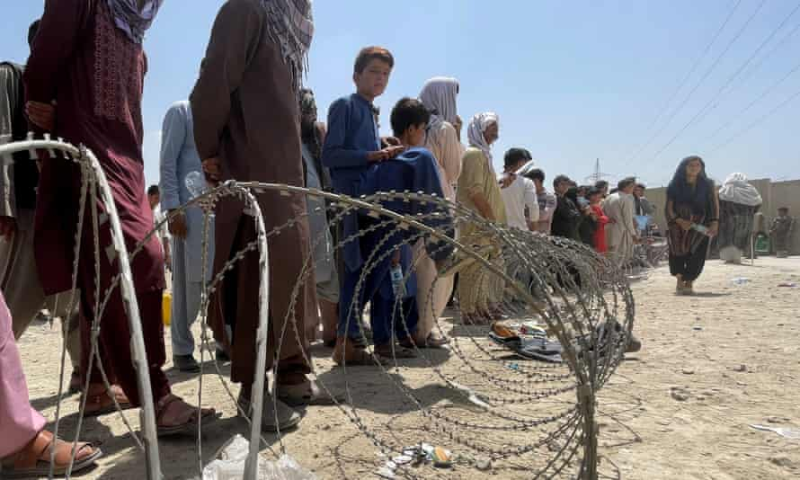 People wait outside Hamid Karzai innternational airport in Kabul, Afghanistan, 17 August.