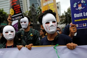Jakarta, Indonesia. Journalists wear masks as they protest near the national monument