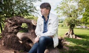 Simon Armitage, CBE, is an English poet, playwright and novelist from Huddersfield, West Yorkshire. Here he poses in a amoungst tree' sin Hay on Wye, UK.