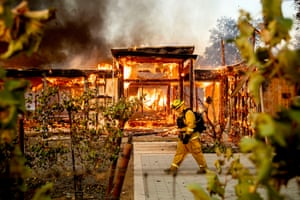 Woodbridge firefighter Joe Zurilgen passes a burning home as the Kincade Fire rages in Healdsburg, California.