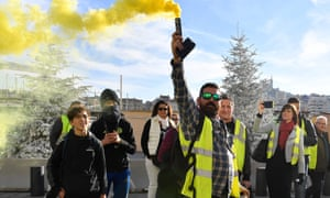 The gilets jaunes hold up a smoke grenade in a demonstration in Marseilles last week