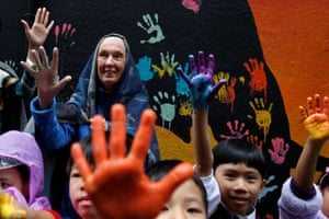 Leading British primatologist, Jane Goodall, poses with school children with hand prints as she attends a campaign to raise awareness on the illegal wildlife trade