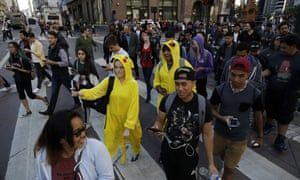 Pokémon Go players walk along Market Street on Wednesday on San Francisco.