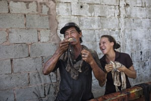 Fisherman Antonio Tello jokes with his daughter Genesis as they clean oil from crabs caught in Lake Maracaibo